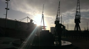 Sun rises above ExCeL and dockers statue